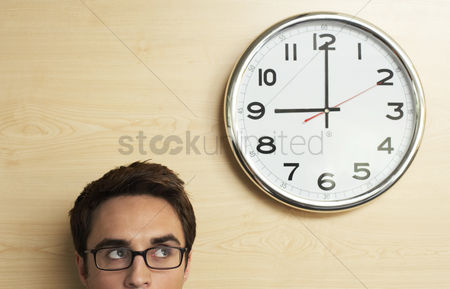 Mid adult man : Cropped image of young businessman in glasses looking up to office clock
