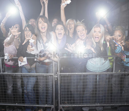 20 24 years : Crowd of young female fans screaming and cheering at concert