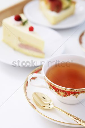 Refreshment : Cup of tea with slices of cake in the background