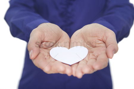 Heart shapes : Cupped hands with a paper heart