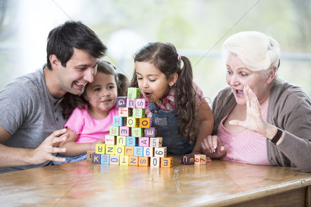 Senior women : Cute girl blowing alphabet blocks while family looking at it in house