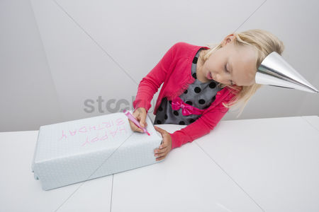 Birthday present : Cute girl writing on birthday gift at table in house
