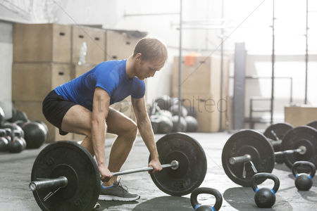 Strong : Dedicated man lifting barbell in crossfit gym