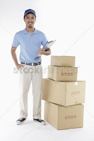 Masculinity : Delivery person standing beside a stack of cardboard boxes