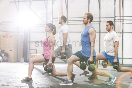 People : Determined people lifting kettlebells at crossfit gym