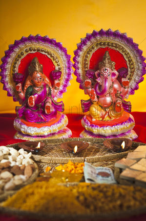 God : Diwali sweets and snacks in front of idols of lakshmi and ganesh during diwali festival
