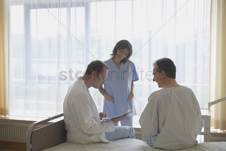 Medical : Doctor and nurse consulting with patient in hospital room