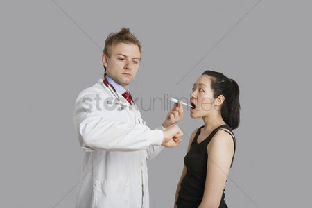 Thermometer : Doctor checking temperature of female patient
