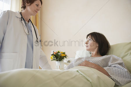 Face : Doctor talking to patient in hospital bed