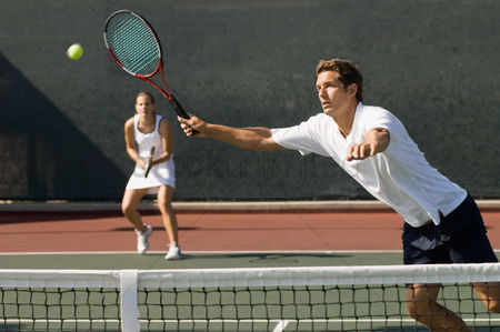 Match : Doubles player stretching hitting tennis ball with forehand near net