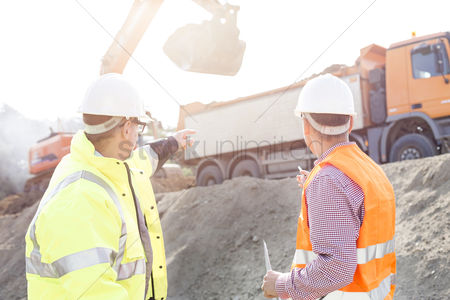 Supervisor : Engineer pointing at vehicles while discussing at construction site