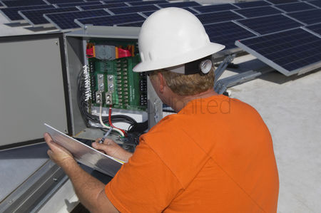 Guys : Engineer working on electrical box at solar power plant