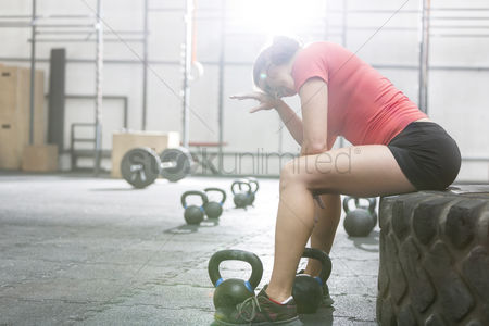 Fitness : Exhausted woman sitting on tire in crossfit gym