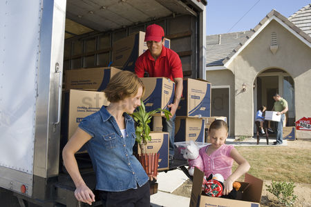 Truck : Family and worker unloading truck of cardboard boxes