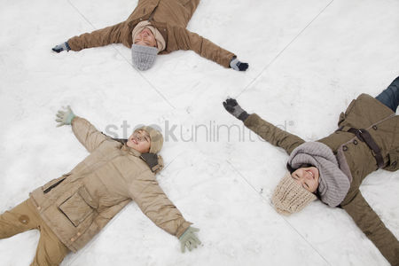 Having fun : Family laying in snow making snow angels
