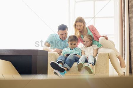 Children playing : Family looking at boy playing hand-held video game at home