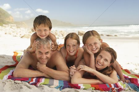 Two people : Family lying on beach