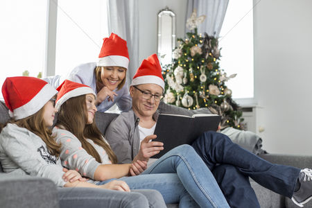Teenager : Family of four reading book in living room during christmas