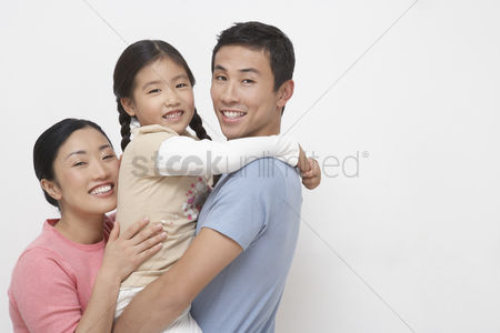 Posed : Family portrait of father holding daughter mother hugging on other side side view