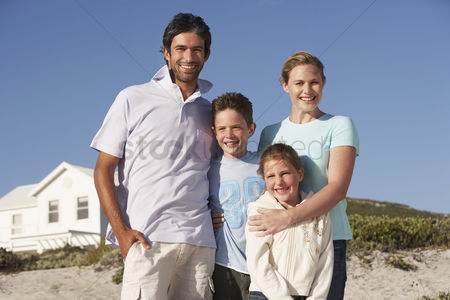 Young boy : Family standing on beach smiling beach house behind