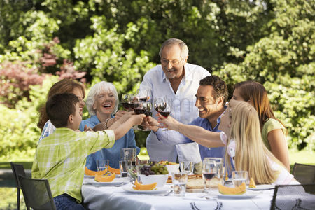 Toasting : Family toasting at lunch table in back yard