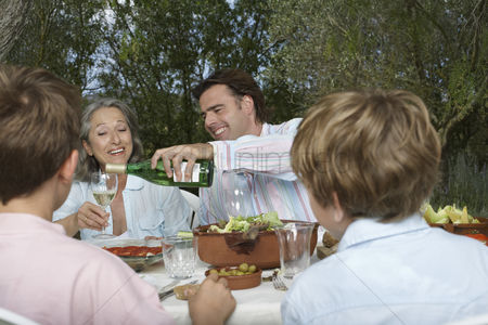 Wine bottle : Family with children  6-11  dining in garden man pouring wine