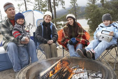 Daughter : Family with two children  7-12  sitting around campfire  portrait