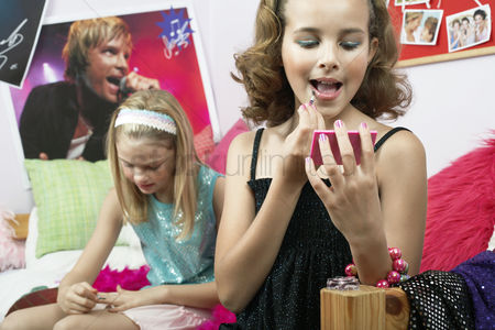 Maturity : Fashionable young girls applying makeup in trendy bedroom