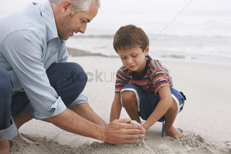 Relationships : Father and son  5-6  playing in sand on beach
