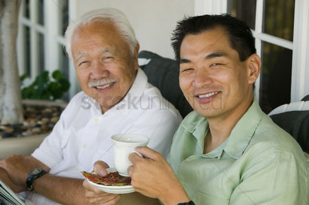 Offspring : Father and son drinking coffee outdoors  portrait