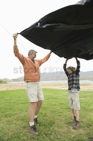 Pitch : Father and son hold groundsheet in wind