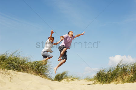 Relationships : Father and son holding hands jumping of sand dune at beach low angle view