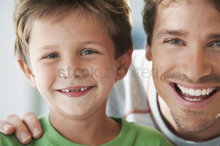 Relationships : Father and son smiling head and shoulders portrait