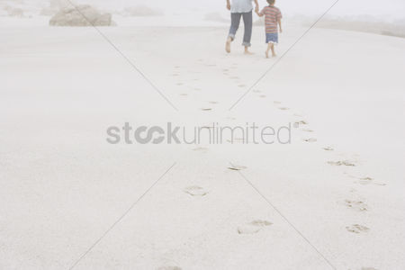 Children : Father and son strolling on beach
