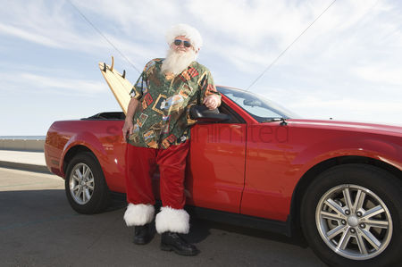 Jacket : Father christmas stands by red convertible with surfboard