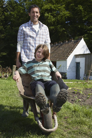 Pushing : Father pushing son  7-9  in wheelbarrow outside cottage portrait