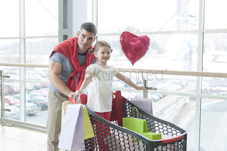 Offspring : Father pushing young daughter in shopping trolley with shopping bags