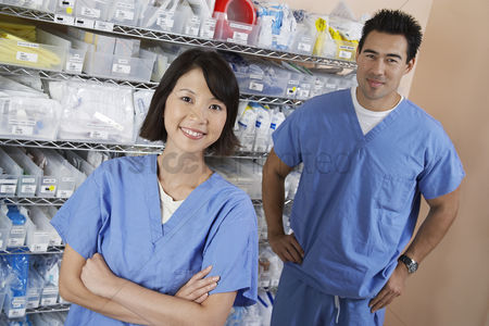 Medication : Female and male nurse standing by shelves with medical supply portrait