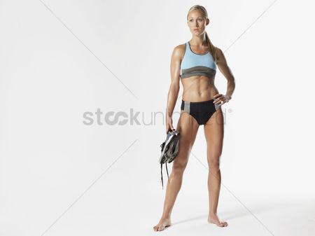 Fitness : Female athlete standing holding shoes portrait