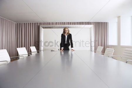 Furniture : Female business executive standing in boardroom