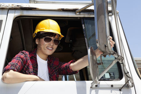 Transportation : Female industrial worker adjusting mirror while sitting in logging truck
