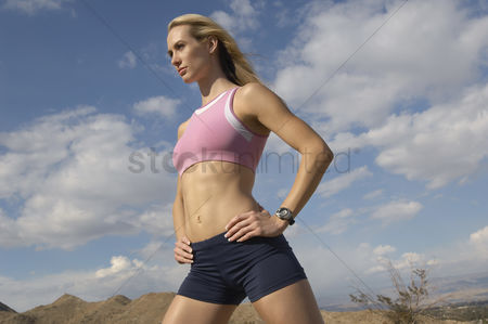 Proud : Female jogger with hands on hips outdoors