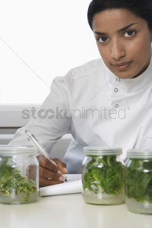 Selection : Female lab worker with glass jars with plant material recording observations
