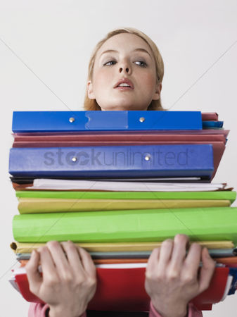 Pile : Female office worker carrying heavy binders close-up