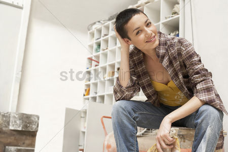 Denim : Female painter on work break in tool room portrait low angle view