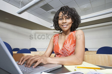 Learning : Female student using laptop in lecture theatre portrait