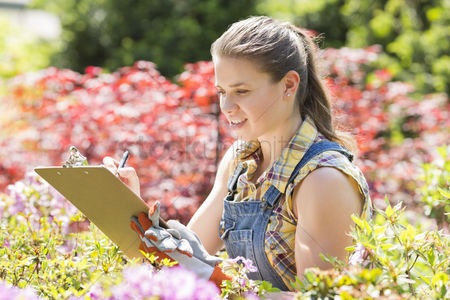 Supervisor : Female supervisor writing on clipboard in garden