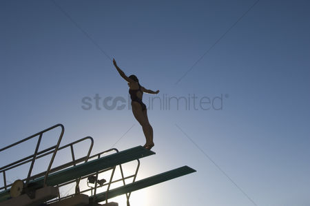 Diving : Female swimmer standing on diving board at sunset