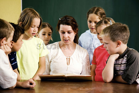 School children : Female teacher reading for her students