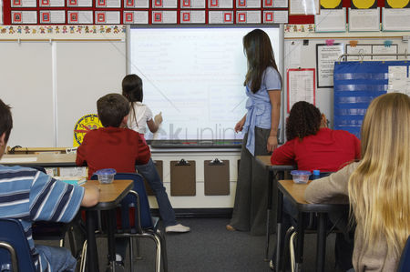 Teacher : Female teacher standing  by whiteboard and assisting schoolgirl